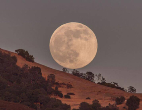 Full Moon rising over hill